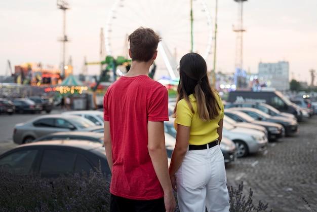 Вид сзади подростков, смотрящих в парк развлечений