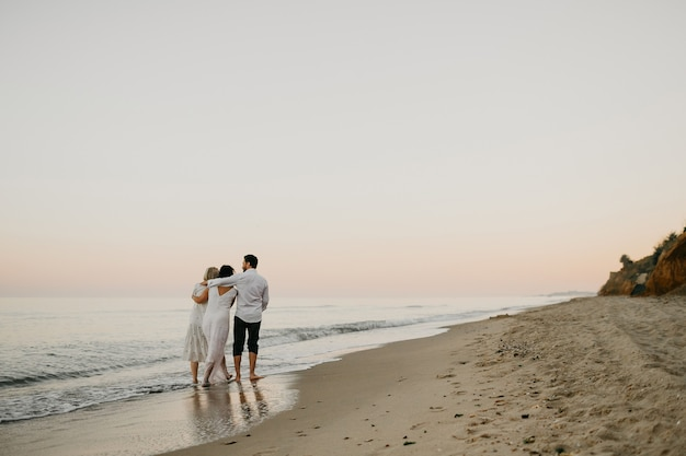 Back view of three adult humans hugging walking on the beach together