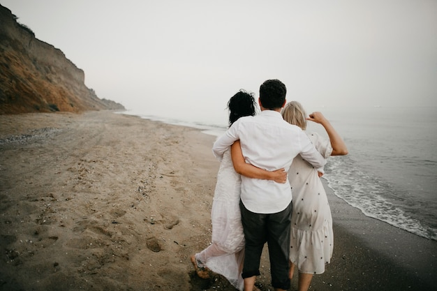 Back view of three adult person hugging on the beach together and looking at ocean