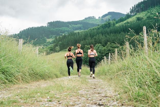 森の中の道を横切って走っている3人の美しい女性の背面図