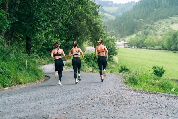 Back view three beautiful women running across a road through a forest