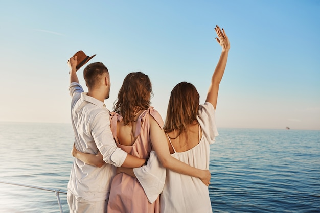 Back view of three best friends travelling by boat hugging and waving while looking at sea. people who are on luxury vacation say hi to ship crue that passes by yacht.