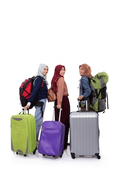 Back view, three hijab woman standing holding suitcase and carrying bag