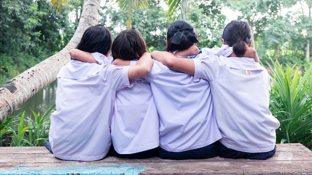 Back view of three students friends hugging with love.