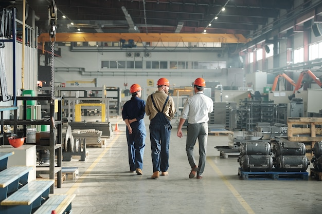 Back view of three young contemporary workers of industrial plant walking along large factory and communicating