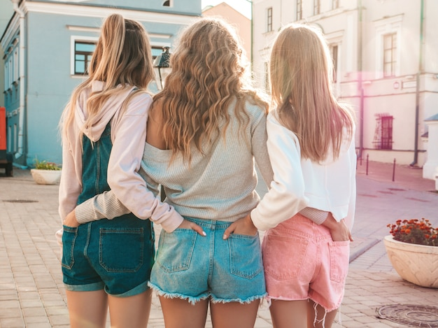 Back view of three young female hipster friends.girls dressed in summer casual clothes.women standing outdoors.they put their hands in shorts in back pockets.posing at sunset