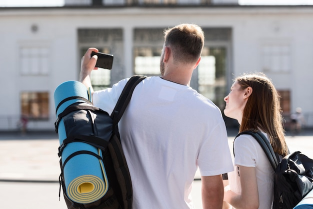 Back view of tourist couple outdoors with backpacks taking selfie