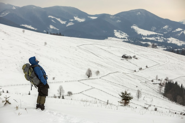 Back view of tourist hiker in warm clothing with backpack standing on mountain clearing