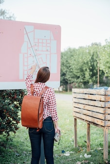 Back view of traveler checking a map