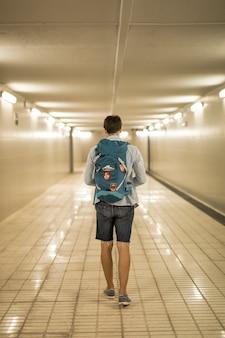 Вид сзади путешественника в подземном переходе