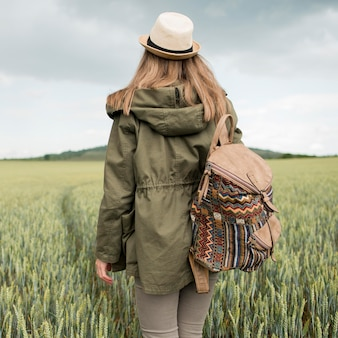 Back view traveller with hat and backpack