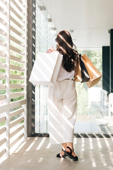 Back view trendy woman holding shopping bags