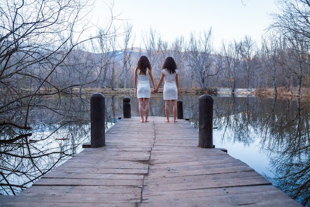 Back view of twin sisters in same white dresses holding hands on wooden pier at calm lake