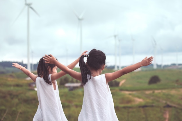 Back view of two asian child girls raise their arms looking at wind turbine field