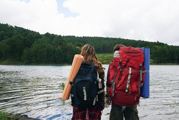 Back view of two hikers with backpacks facing water