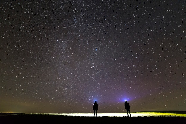 Back view of two men with head flashlights under dark starry sky.