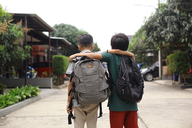 Back view of two students embrace each other going to school
