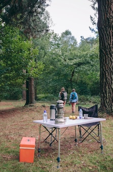 Back view of two unrecognizable women hiking in the forest with camping table in the foreground. focus on people.
