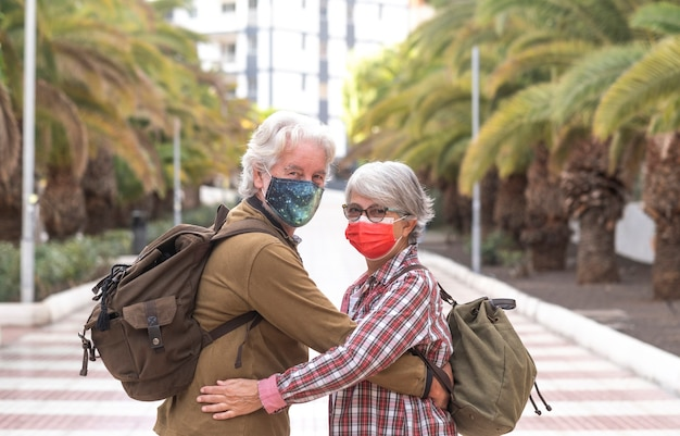 Back view of two whitehaired traveler people looking at camera while walking together in the city