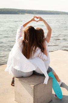 Back view of two women making the love sign by the lake