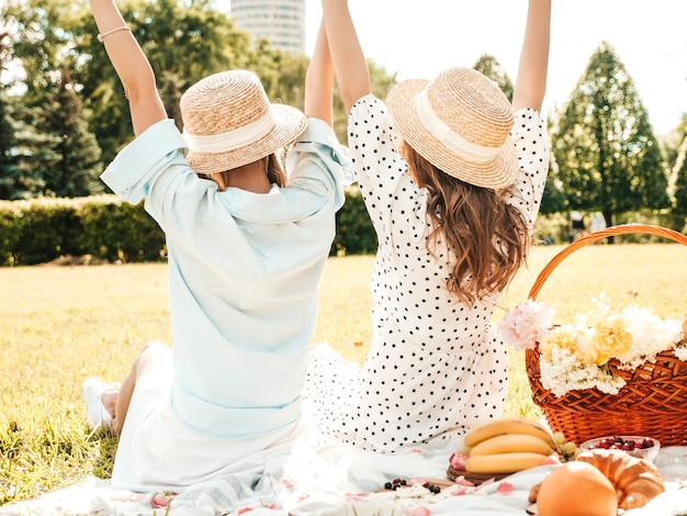Back view of two young beautiful smiling female in trendy summer sundress and hats.carefree women making picnic outside.