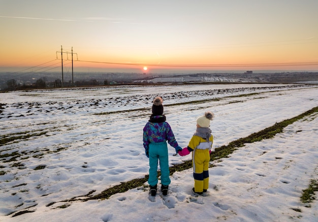 Back view of two young children in warm clothing standing in frozen snow field holding hands on copy space background of setting sun and clear blue sky.