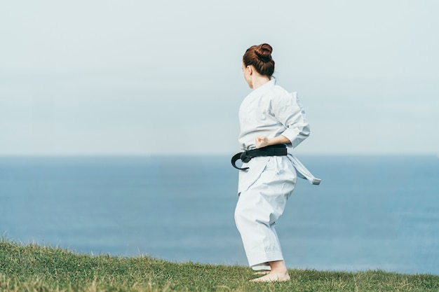 Back view of unknown young female redhead karate athlete training on top of cliff with sea on background