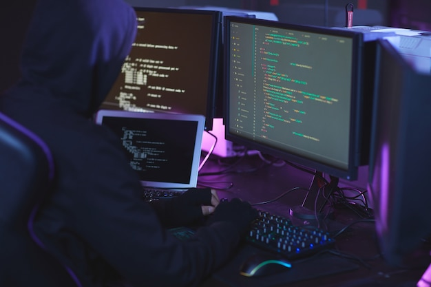 Back view of unrecognizable cyber security hacker wearing hood while working on programming code in dark room, copy space