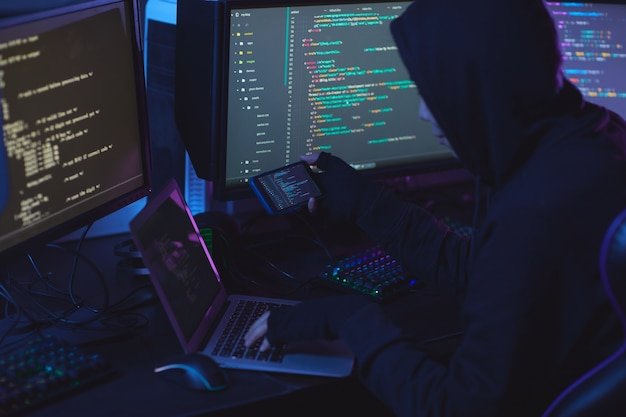Back view at unrecognizable cyber security hacker wearing hood while working on programming in dark room, copy space