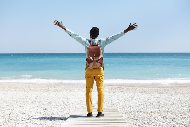 Back view of unrecognizable dark-skinned european man standing on boardwalk on tropical beach feeling happy and free while seeing ocean for the first time during summer trip, keeping arms wide open