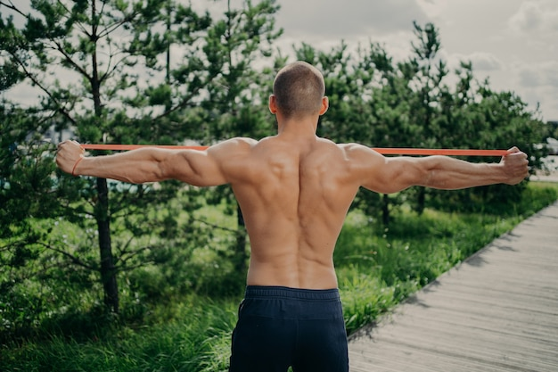Back view of unrecognizable sportsman stretches elastic resistance band