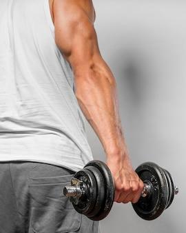 Vista posteriore dell'uomo molto in forma che tiene il peso