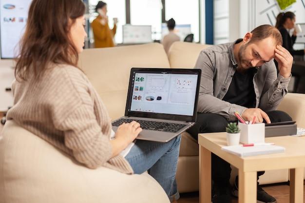 Вид сзади видео молодой деловой женщины, сидящей на диване в офисе, используя портативный компьютер с графикой, в то время как коллеги работают на фоне