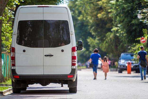 背面図の白い乗客中型商業高級ミニバスバンが夏の街に駐車。