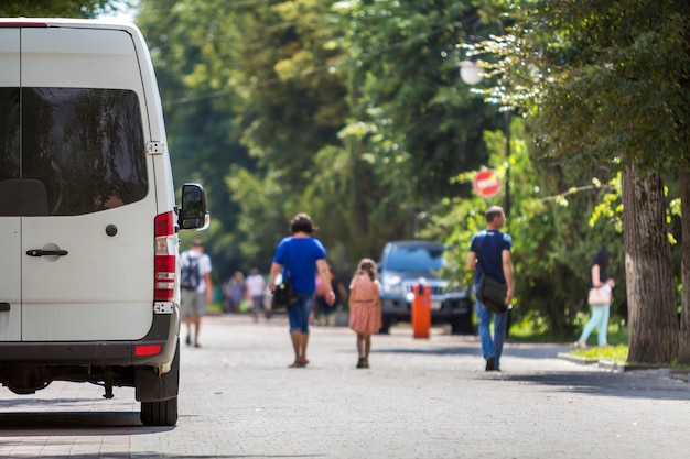 Back view of white passenger medium-size commercial luxury minibus van parked
