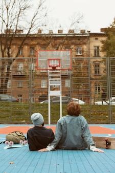 Вид сзади женщина и мужчина, глядя на баскетбольное поле