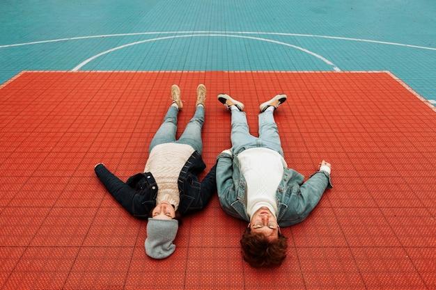 バスケットボールのフィールドに横たわっている女性と男性の背面図