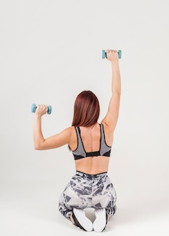 Back view of woman in athleisure exercising with weights