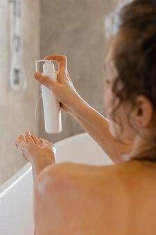 Donna vista posteriore nella vasca da bagno con lozione