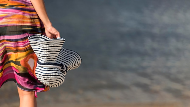 Back view of woman at the beach holding hat