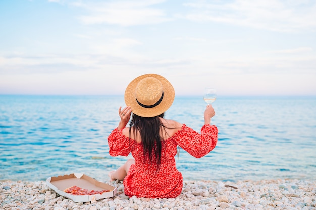 Back view of woman on the beach on picnic with glass of wine and pizza