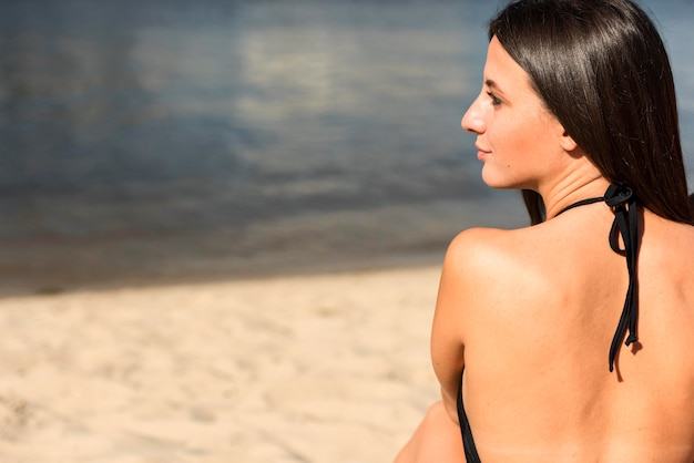 Back view of woman at the beach with copy space
