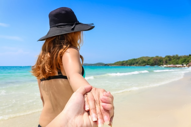 Back view of a woman in bikini with her hat taking a walk holding her couple hands on the beach