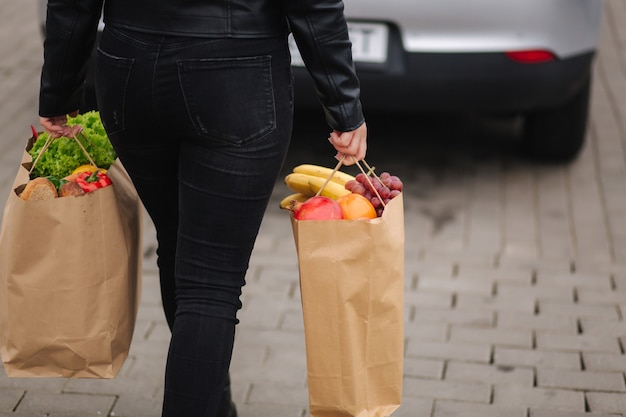 Back view of woman in black clothes carries a eco package full of groceries to the car