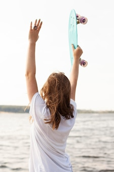 Back view of woman by the lake holding skateboard