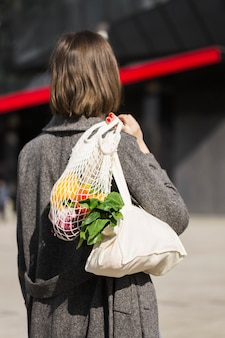 Back view woman carrying eco friendly bag with organic vegetables