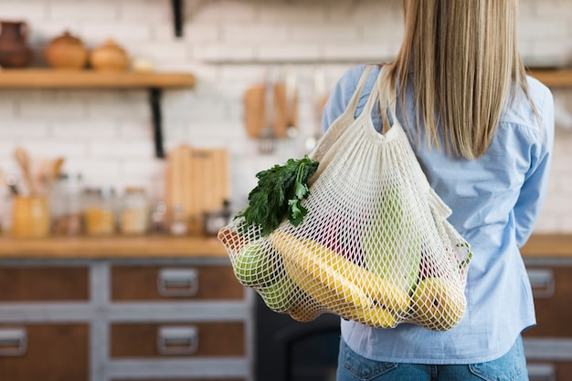 Back view woman carrying reusable bag with organic fruits