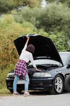Back view of woman checking engine