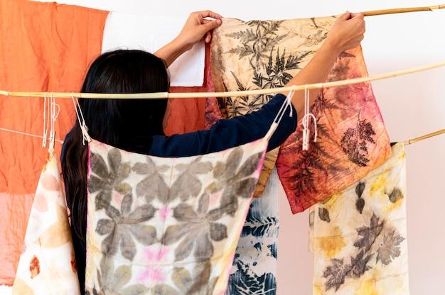 天然色素布をチェックする背面図の女性
