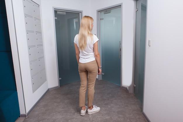 開くドアを選択する背面図の女性